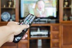 Mano que sostiene la TV teledirigida con la televisión Fotos de archivo libres de regalías