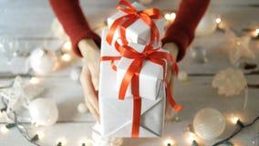 Mano que sostiene las cajas de regalo blancas con la decoración de la Navidad almacen de video