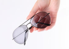 Mano que sostiene las gafas de sol grises Fotografía de archivo