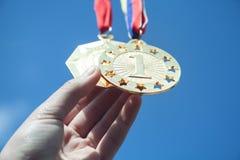 Mano que sostiene las medallas de oro Éxito, logro, metas imagenes de archivo
