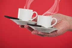 Mano que sostiene las tazas del café express Imagenes de archivo