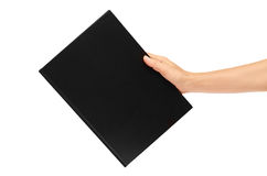Mano que sostiene los cuadernos aislados en el fondo blanco Fotos de archivo libres de regalías