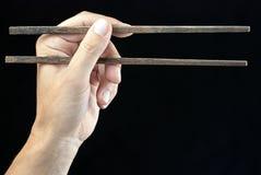 Mano que sostiene los palillos Fotografía de archivo