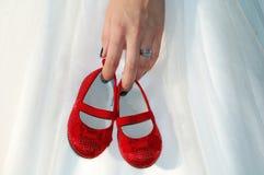 Mano que sostiene los pequeños zapatos rojos Imagen de archivo