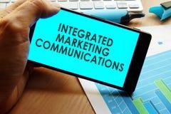 Mano que sostiene smartphone con comunicaciones de comercialización integrada de las palabras imagen de archivo libre de regalías