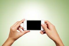 Mano que sostiene smartphone con la pantalla en blanco aislado imágenes de archivo libres de regalías