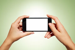 Mano que sostiene smartphone con la pantalla en blanco aislado imagen de archivo