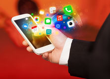Mano que sostiene smartphone con los iconos coloridos del app fotografía de archivo libre de regalías