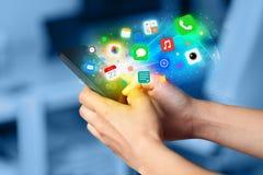 Mano que sostiene smartphone con los iconos coloridos del app Foto de archivo libre de regalías