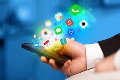 Mano que sostiene smartphone con los iconos coloridos del app Imagen de archivo libre de regalías