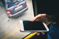 Mano que sostiene smartphone en transporte público Fotos de archivo libres de regalías