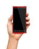 Mano que sostiene Smartphone rojo con la pantalla en blanco Fotos de archivo
