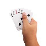 Mano que sostiene tarjetas del póker en el fondo blanco Foto de archivo