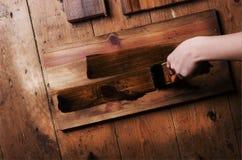 Mano que sostiene un cepillo de pintura que aplica la pintura del barniz en un de madera Imagen de archivo