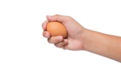 Mano que sostiene un huevo aislado en blanco Foto de archivo libre de regalías