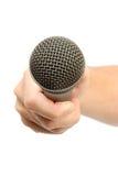 Mano que sostiene un micrófono Foto de archivo libre de regalías