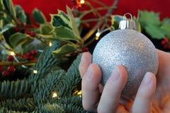 Mano que sostiene un ornamento de plata de la Navidad del brillo Imagen de archivo libre de regalías