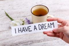 Mano que sostiene un papel con una inscripción tengo un sueño, contra una tabla con una taza de té negro y de flores imagen de archivo libre de regalías