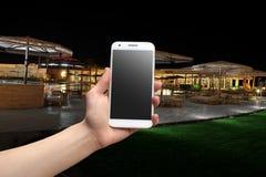 Mano que sostiene un teléfono en la noche Imagen de archivo libre de regalías