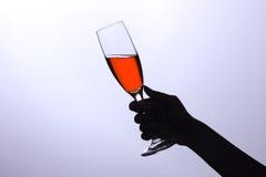 Mano que sostiene un vidrio con el vino Foto de archivo libre de regalías