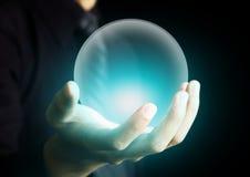 Mano que sostiene una bola de cristal que brilla intensamente Foto de archivo