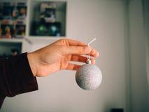 Mano que sostiene una bola de plata de la Navidad foto de archivo