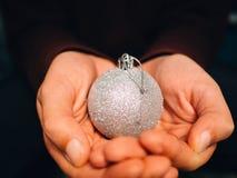 Mano que sostiene una bola de plata de la Navidad imagenes de archivo