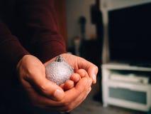 Mano que sostiene una bola de plata de la Navidad fotografía de archivo libre de regalías