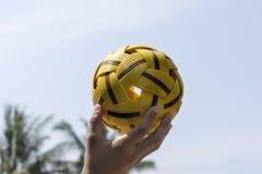 Mano que sostiene una bola de Takraw Fotografía de archivo