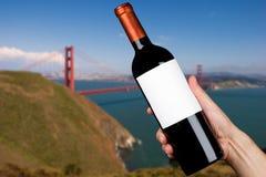 Mano que sostiene una botella de vino Foto de archivo