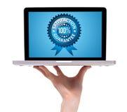 Mano que sostiene una computadora portátil con garantía de la satisfacción Fotografía de archivo