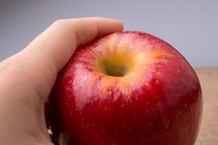 Mano que sostiene una manzana roja en la madera Foto de archivo