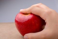 Mano que sostiene una manzana roja en la madera Fotografía de archivo