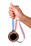 Mano que sostiene una medalla Imagenes de archivo