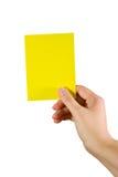 Mano que sostiene una tarjeta amarilla Fotos de archivo