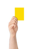 Mano que sostiene una tarjeta amarilla fotos de archivo libres de regalías