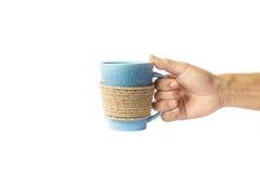 Mano que sostiene una taza de café envuelta cuerda Foto de archivo libre de regalías