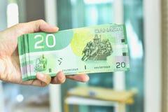 Mano que sostiene veinte billetes de banco canadienses del dólar imagen de archivo