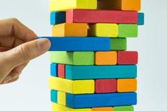 Mano que tira del bloque de madera colorido de la torre adentro como riesgo o fotografía de archivo