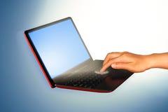 Mano que toca en el ordenador portátil y la conexión Imágenes de archivo libres de regalías