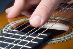 Mano que toca la guitarra Imagen de archivo libre de regalías