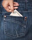 Mano que toma el dinero del bolsillo Foto de archivo