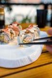 Mano que toma el rollo de sushi con los palillos Imagen de archivo libre de regalías