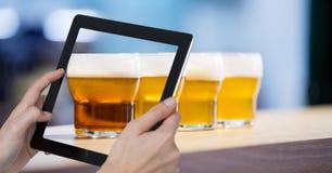 Mano que toma la imagen de los vidrios de cerveza con la tableta digital en barra Foto de archivo libre de regalías