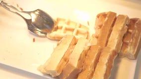 Mano que toma las galletas belgas que mienten en la placa blanca en buffet en restaurante del hotel Galletas cocidas dulces para  almacen de video
