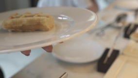 Mano que toma las galletas belgas y que pone en la placa blanca en buffet en restaurante del hotel Galletas cocidas dulces para l almacen de video