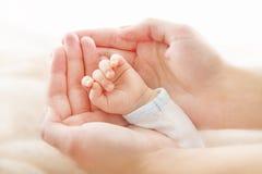 Mano recién nacida del bebé en manos de la madre. Concepto del asistance de la ayuda imagen de archivo libre de regalías