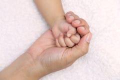 Mano recién nacida del bebé en palma de la mamá Imagen de archivo