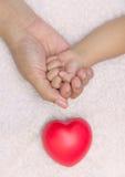 Mano recién nacida del bebé en palma de la mamá con el corazón rojo Imágenes de archivo libres de regalías