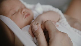 Mano recién nacida del bebé que sostiene el finger adulto almacen de metraje de vídeo